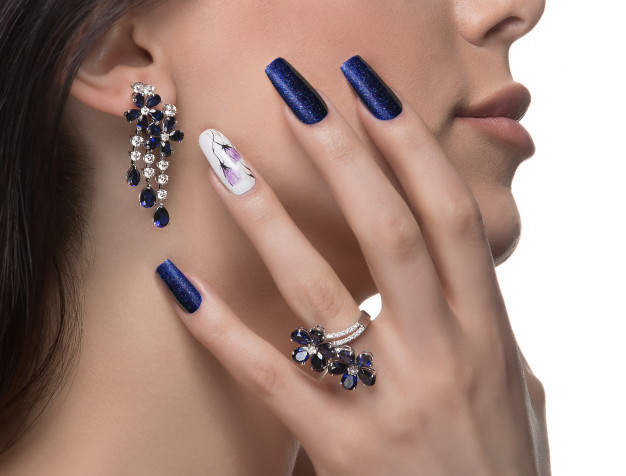 woman-with-nail-art-promoting-design-luxury-earrings-ring_114579-3704